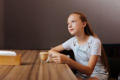 Blonde-haired teenager drinking decaf latte in cafe. Blonde-haired teenager. Blonde-haired teenager wearing white shirt drinking decaf latte while sitting in stock image