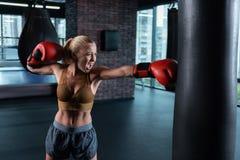Blonde-haired vrouwelijke bokser die aardige abs hebben die hard in dozen doen royalty-vrije stock foto's