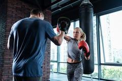 Blonde-haired vrouwelijke bokser met aardige abs die doosles hebben stock foto's