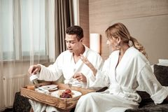 Blonde-haired wife wearing white bathrobe talking to husband. Talking to husband. Blonde-haired wife wearing white bathrobe talking to husband having his tasty royalty free stock image