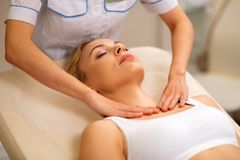 Blonde-haired woman closing eyes while having neck massage royalty free stock photography