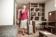 Blonde-haired woman coming to hotel room with her luggage royalty free stock images