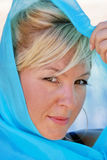 Blonde haired woman in silk. Beautiful blonde haired woman wrapped in blue silk looking at viewer Stock Image