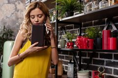 Blonde-haired woman wearing yellow blouse smelling spices in the kitchen royalty free stock images
