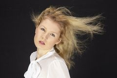 Blonde-haired woman with white blouse in a storm (wind machine) Stock Photo