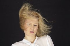 Blonde-haired woman with white blouse in a storm (wind machine) Royalty Free Stock Image