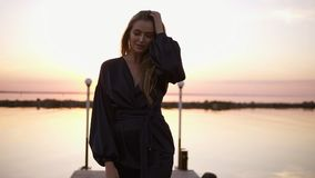 Blonde haired young caucasian woman, model in black clothes kimono walking by the pier. Morning pink light. Seaside stock footage