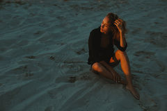 Blonde Haired Young Woman Posing In Sands Of Desert Lit By Red Setting Sun Light Stock Photos