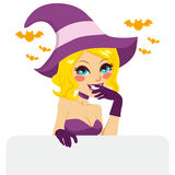 Blonde Halloween Witch. Naughty blonde woman with purple and pink Halloween witch costume smiling holding an empty billboard Royalty Free Stock Photography