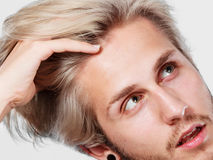 Blonde handsome guy touching his hair. Hairstyle, haircare concept. Blonde handsome guy wearing grey t shirt touching his hair, close up studio shot white Royalty Free Stock Photography