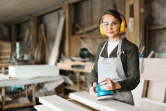 Blonde Handwerkerin mit elektrischer Sandpapierschleifmaschine Lizenzfreie Stockfotografie