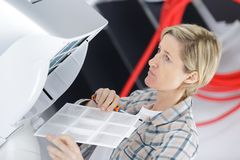 Blonde handywoman cleaning fixing ventilation system. Woman stock photography