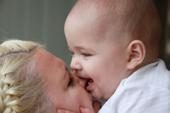 Blonde happy beautiful mother with her little baby against green background Stock Photos