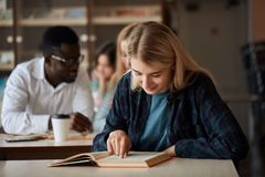 Blonde happy beautiful woman female student attends university classes indoors. stock photos