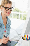Blonde happy designer using digitizer at her desk Royalty Free Stock Photo