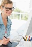 Blonde happy designer using digitizer at her desk Royalty Free Stock Photo