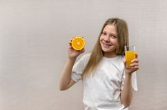 Blonde happy girl holds in her hand a glass of fresh juice. Healthy diet. Veggie and vegan royalty free stock image