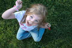 Blonde happy girl portrait playing with gras on lawn Royalty Free Stock Photos