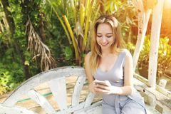 Blonde happy woman uses smartphone for work on sunny day, background of sunshine green palms in Thailand, Phuket travel stock photos
