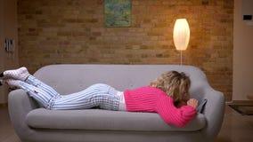 Blonde Hausfrau in der rosa Strickjacke, die auf Magen auf dem Sofa surft in Smartphone in der gemütlichen Hauptatmosphäre liegt stock video