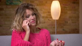 Blonde Hausfrau des Nahaufnahmeschusses in der rosa Strickjacke auf Sofa emotional sprechend auf Smartphone in der gemütlichen Ha stock footage