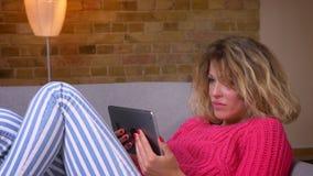 Blonde Hausfrau des Nahaufnahmeschusses in der rosa Strickjacke, die auf Sofa sprechend im videochat auf Tablette in der gemütlic stock video footage
