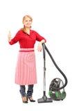 Blonde Hausfrau, die auf einem Staubsauger aufwirft und Daumen aufgibt Lizenzfreies Stockbild