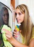 Blonde Hausfrau, die Fernsehen säubert Stockfotografie