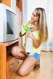 Blonde Hausfrau, die Fernsehen säubert Stockbild