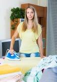 Blonde Hausfrau, die mit Eisen bügelt Lizenzfreies Stockbild