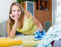 Blonde Hausfrau, die mit Eisen bügelt Lizenzfreie Stockbilder
