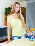 Blonde Hausfrau, die mit Eisen bügelt Stockfotografie