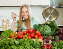 Blonde Hausfrau, die mit Frischgemüse kocht Lizenzfreie Stockbilder