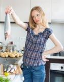 Blonde Hausfrau, die Seebarsch kocht Stockfotos