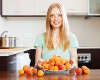 Blonde Hausfrau mit frischen Aprikosen Stockbild