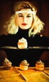 Blonde Hausfrau und kleine Kuchen der Weinlese mit Messern Stockbild