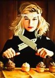 Blonde Hausfrau und kleine Kuchen mit Messern Stockfotos