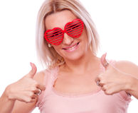 Blonde with heart-shape glasses showing thumbs up Stock Image