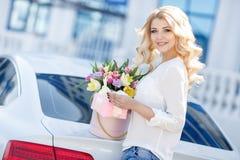 Blonde hermoso con las flores en caja de regalo imagen de archivo