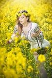 Blonde hermoso con los ojos azules que sonríe y que goza de las flores amarillas brillantes de la rabina Imagenes de archivo