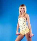 Blonde hermoso con pesas de gimnasia a disposición Foto de archivo libre de regalías