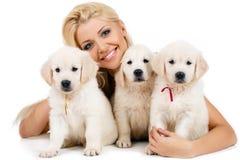 Blonde hermoso con un pequeño perrito blanco de Labrador fotografía de archivo