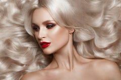 Blonde hermoso de una manera de Hollywood con los rizos, el maquillaje natural y los labios rojos Cara y pelo de la belleza fotos de archivo libres de regalías