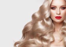 Blonde hermoso de una manera de Hollywood con los rizos, el maquillaje natural y los labios rojos Cara y pelo de la belleza imagen de archivo libre de regalías