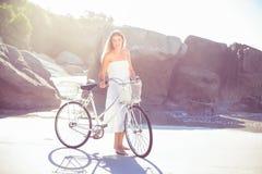 Blonde hermoso en los sundress blancos que se colocan con la bici en la playa Imágenes de archivo libres de regalías