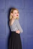 Blonde hermoso en un camisa-chaleco cerca de la pared Imagenes de archivo