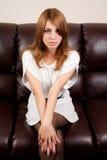 Blonde hermoso en un sofá de cuero Imágenes de archivo libres de regalías