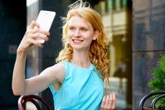 Blonde hermoso joven con el pelo rizado que toma el selfie en smartphone Fotografía de archivo libre de regalías
