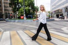 Blonde hermoso que cruza el camino con la taza de takeaway del café Imágenes de archivo libres de regalías
