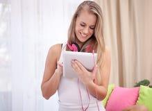 Blonde hermoso que mira la tableta digital en la cama Foto de archivo